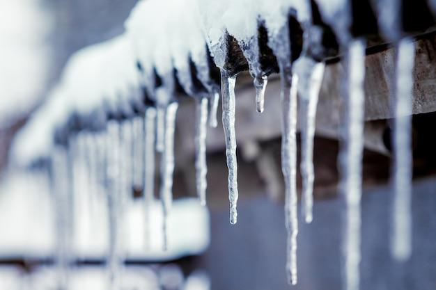 Pingentes de gelo pendurados no telhado da casa. dia quente de inverno