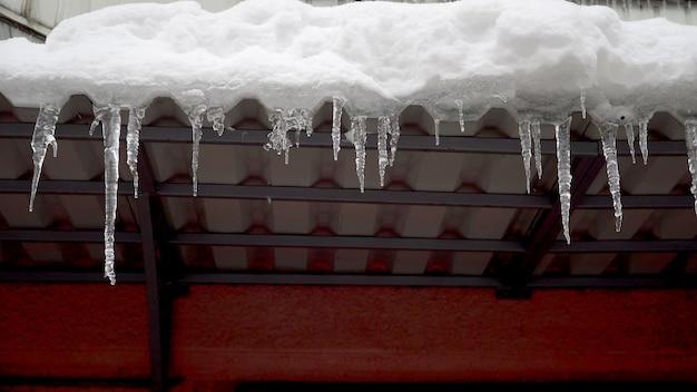 Pingentes de inverno derretendo no telhado sob o sol da primavera e pingando de suas pontas