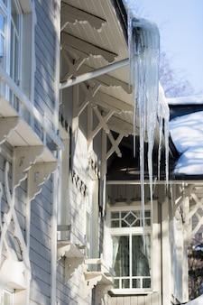 Pingentes pendurados no telhado de um edifício de madeira no inverno em tempo ensolarado