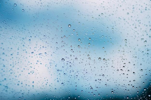 Pingo de chuva abstrata no vidro e céu azul turva no fundo