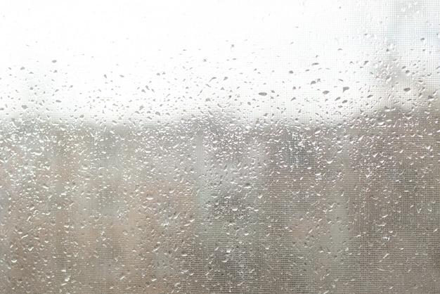 Pingos de chuva na superfície de vidros de janela com fundo nublado