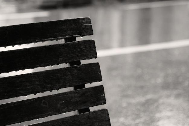 Pingos de chuva no banco em um dia chuvoso. conceito de solitário, triste, sozinho.