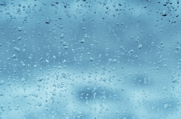 Pingos de chuva no vidro da janela, em tons de azul