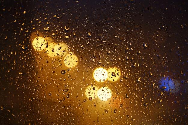 Pingos de chuva textura no vidro, céu noturno e luzes da cidade em bokeh