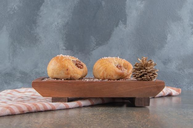 Pinha ao lado de dois deliciosos biscoitos na placa de madeira no mármore.