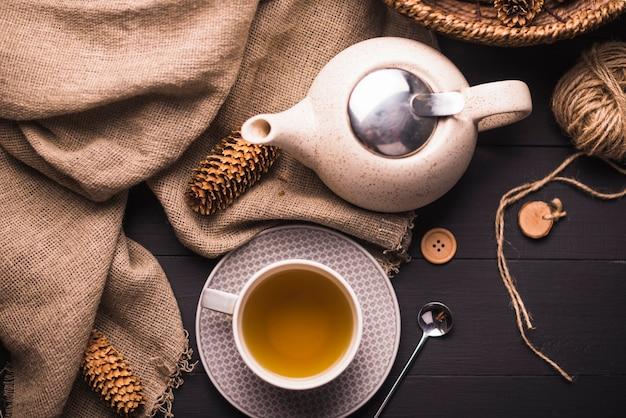 Pinha; chá; bule de chá; saco; botão e novelo de lã na mesa