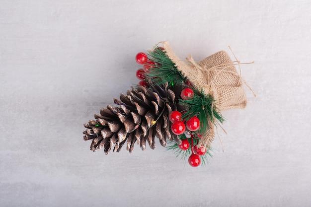 Pinha decorada com bagas de azevinho e floco de neve na mesa branca.