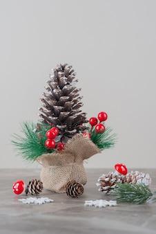 Pinha decorada com bagas de azevinho e galhos na mesa de mármore.