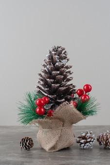 Pinha decorada com bagas de azevinho e ramos na mesa de mármore