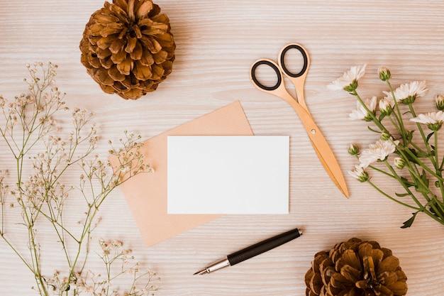 Pinha; tesoura; aster e flores de respiração do bebê; caneta e cartão em branco na mesa de madeira