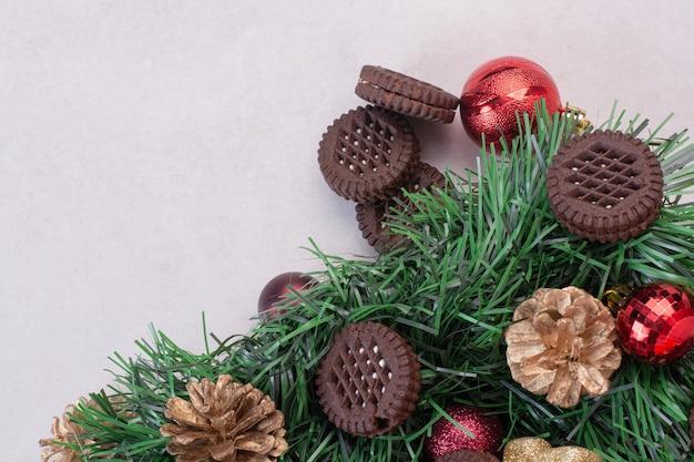 Pinhas com bolas de natal e biscoito na superfície branca