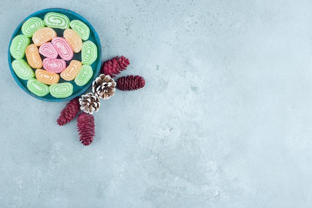 Pinhas com geleias de frutas açucaradas na placa de madeira azul.