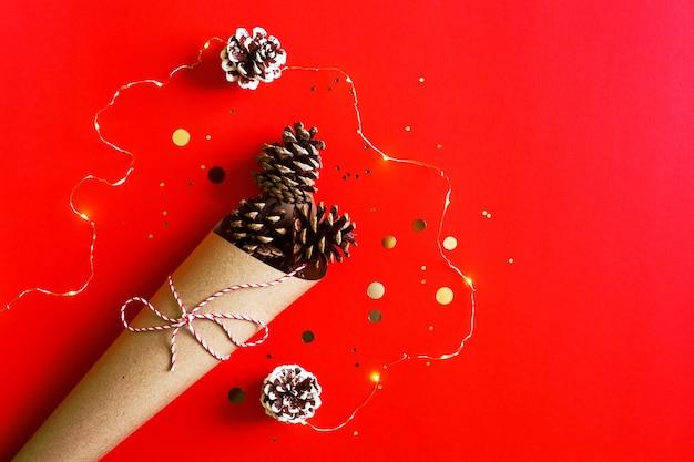 Pinhas em cone de papel com luzes, vista superior vermelha vívida de natal