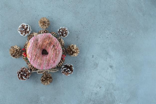 Pinhas em torno de um donut em uma coroa de flores na superfície de mármore