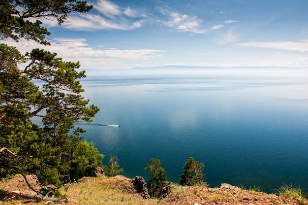 Pinheiro acima do lago baikal com pequeno navio em um dia ensolarado
