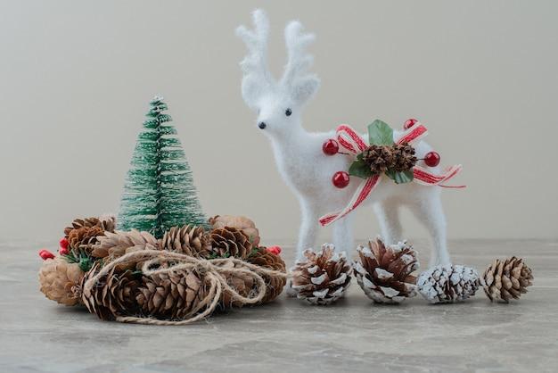 Pinheiro, cones e cervos de brinquedo na mesa de mármore.