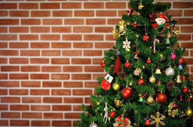 Pinheiro de natal verde decorando com enfeites pendurados brilhantes brilho esfera bolas papai noel boneca vara sinos modelo rena flocos de gelo estrela tambor na frente turva fundo da parede de tijolo.