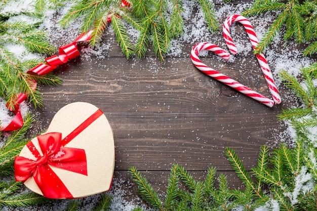 Pinheiros de natal na neve com bastões de doces, fita vermelha e caixa de presente em forma de coração em uma placa de madeira escura.