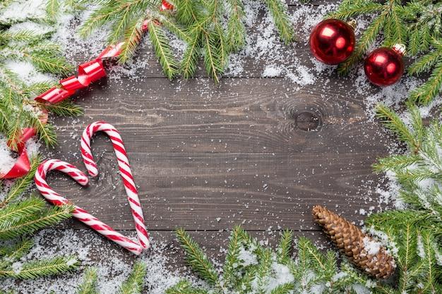 Pinheiros de natal na neve com cone, fita vermelha, bolas vermelhas de natal e bastões de doces em uma placa de madeira escura