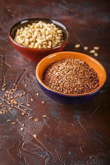 Pinhões e sementes de linho em tigelas de cerâmica