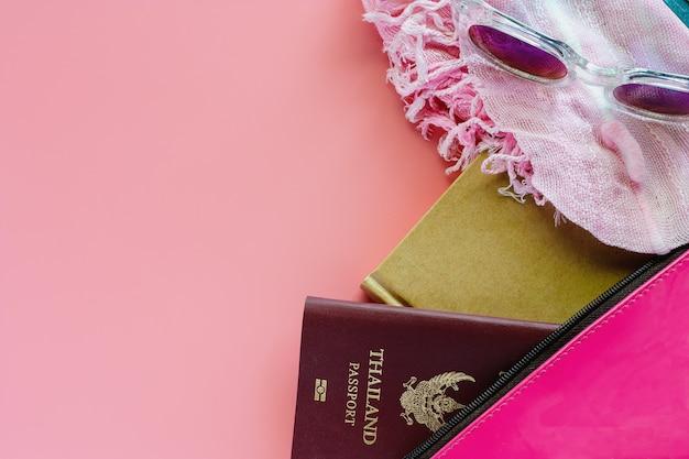 Pinky saco com passaporte, notebook, óculos escuros e lenço no fundo rosa