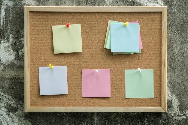 Pino de nota de papel na placa de cortiça. notas em branco para adicionar mensagem de texto. nota de adesivo.