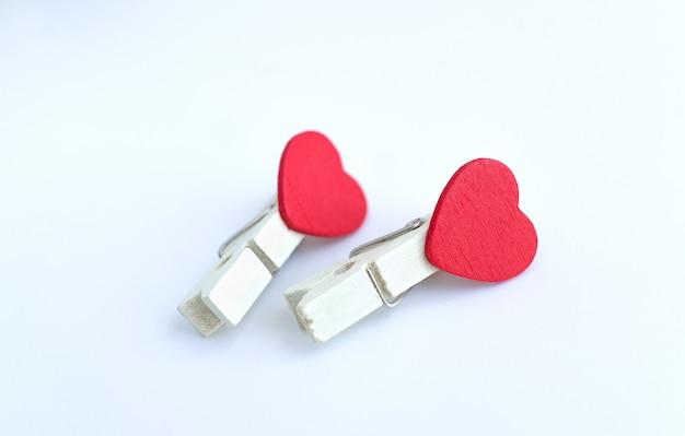 Pino de roupa de madeira ou pinos de pano com design de forma de coração em um fundo branco
