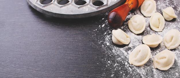Pino do rolo, bolinhas de massa cruas na farinha em um fundo preto copie o espaço.