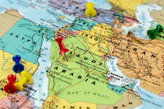 Pino vermelho colocado no mapa da arábia saudita e irã. viagem e destino.