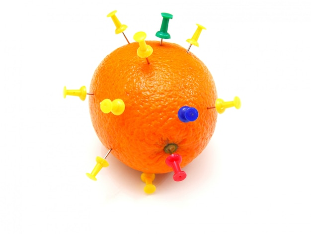 Pinos coloridos isolados do escritório empurrados em uma laranja
