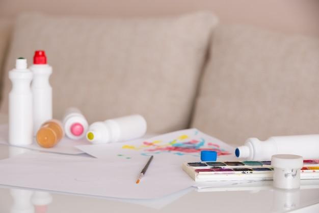 Pinta, pincéis, papel e outros suprimentos fixos na mesa branca