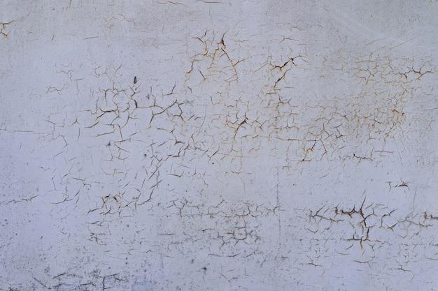 Pintado em metal rachado velho branco enferrujado fundo.
