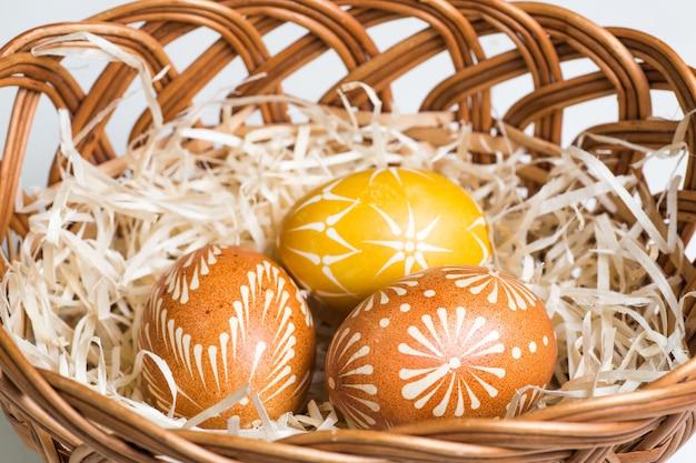 Pintados à mão ovos de páscoa na cesta marrom