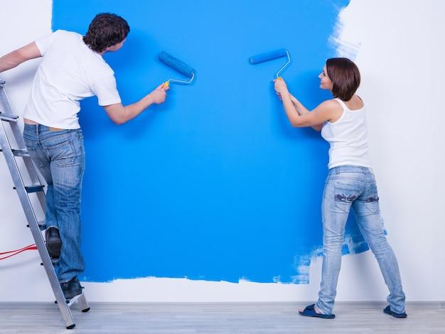 Pintando a parede de azul por um jovem casal em roupas casuais