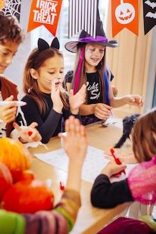 Pintando fotos. muitas crianças bonitas e felizes vestindo fantasias de halloween brilhantes e engraçadas pintando fotos