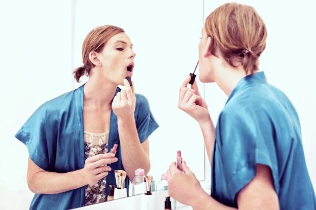 Pintando o rosto masculino. transgênero atraente e preciso abrindo amplamente a boca durante o revestimento com a cor rosa
