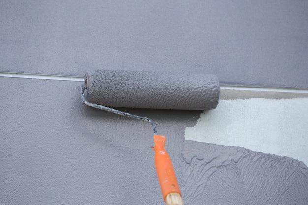 Pintando uma parede com rolo de pintura