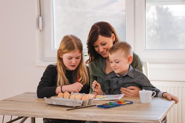 Pintar ovos de páscoa, mãe e filhos se divertindo muito