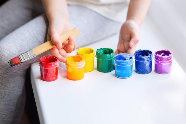 Pinte as cores do arco-íris, as mãos das crianças com um pincel e tintas.