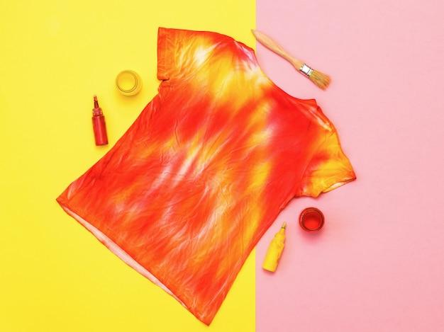 Pinte e pincele com uma camiseta no estilo hippie. tecido tingido em estilo tie dye. postura plana.