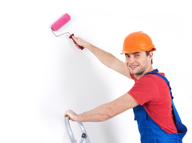 Pintor artesão fica na escada com rolo, retrato sobre fundo branco