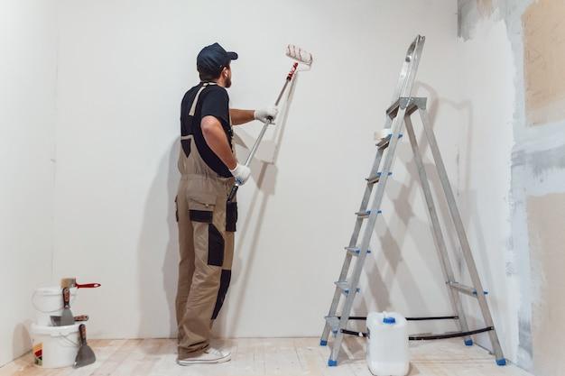 Pintor bonito com rolo de pintura em uma sala vazia pinta a parede