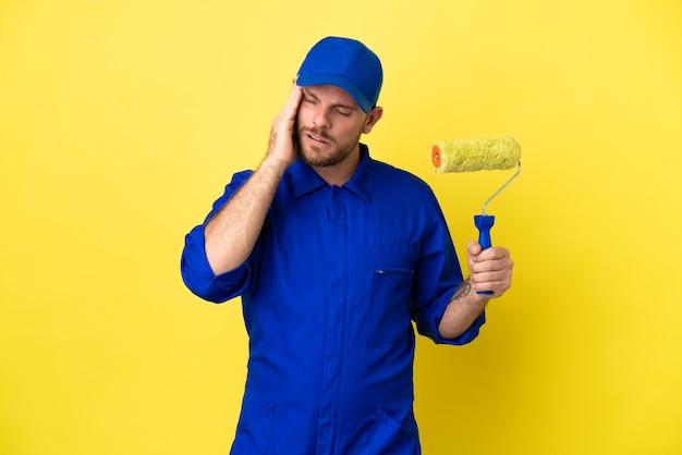 Pintor brasileiro isolado em fundo amarelo com dor de cabeça