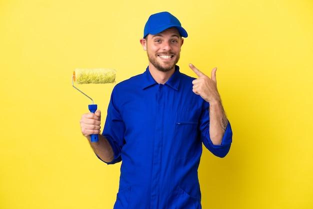 Pintor brasileiro isolado em fundo amarelo fazendo gesto de polegar para cima