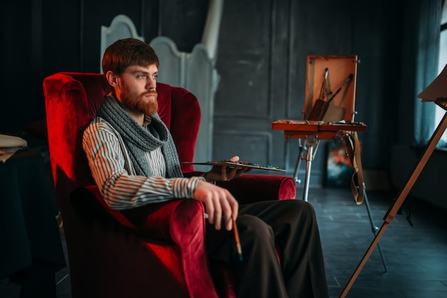 Pintor com paleta e pincel na mão sentado em uma cadeira, estúdio de arte no fundo