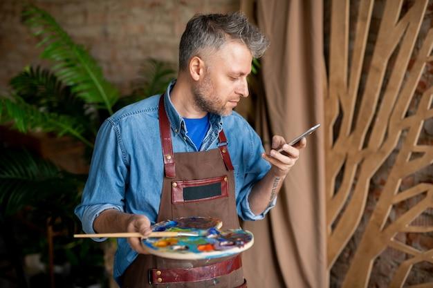 Pintor criativo contemporâneo com paleta e pincel de rolagem no smartphone ou mensagens no estúdio