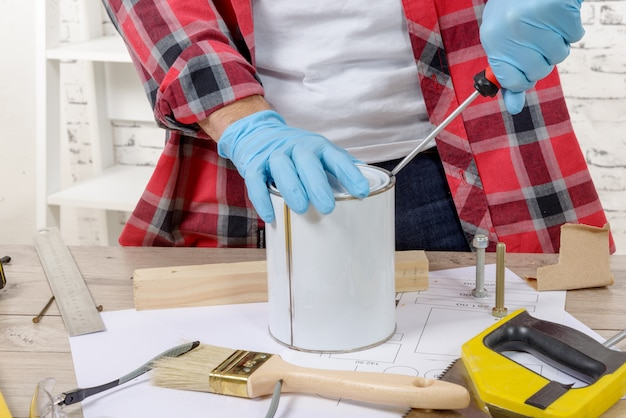 Pintor de casa abre uma lata de tinta com uma chave de fenda