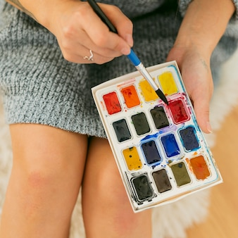 Pintor de close-up segurando a paleta da bandeja de cores