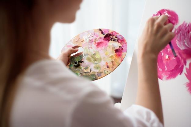 Pintor de desenho no estúdio de arte usando cavalete. retrato, jovem, mulher, pintura, óleo, tintas, lona branca, vista lateral, retrato