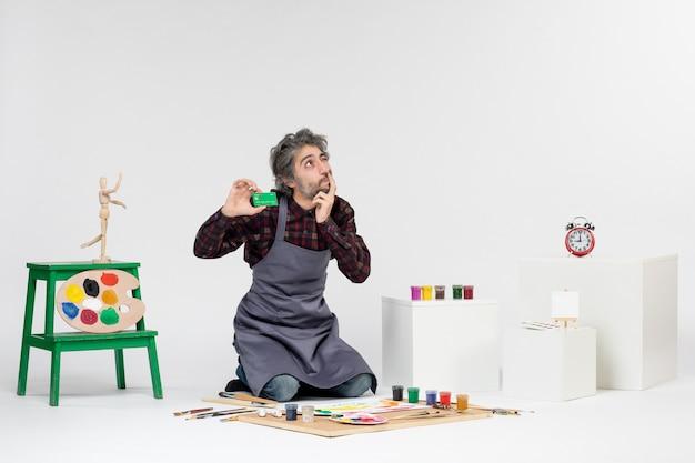 Pintor de frente para o homem segurando um cartão de banco verde no fundo branco imagem arte pintura colorida artista trabalho dinheiro